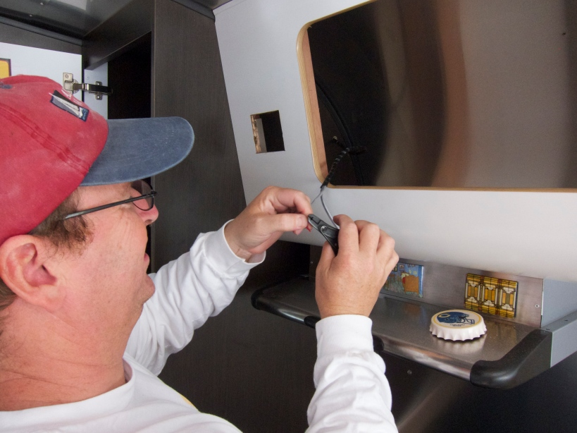 Tim preps the 18/2 wire which powers the remote panel.  Note the square hole for the panel